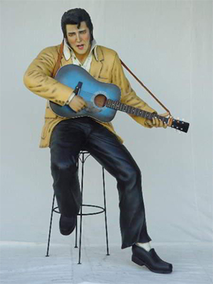 Elvis Presley sitting on stool playing guitar