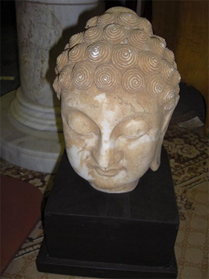 Stone Buddha head with pedestal